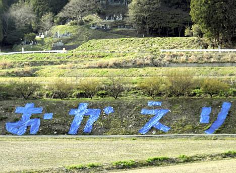 「じじい部隊」が町民を迎えるためにシートで描いた「おかえり」=福島県大熊町大川原で、乾達撮影