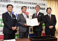 締結式で記念撮影する高知銀行の森下頭取(左から2人目)ら=高知市の高知銀行本店で、郡悠介撮影