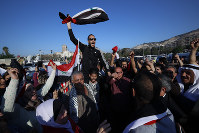Syrian government supporters chant slogans against U.S. President Trump during demonstrations following a wave of U.S., British and French military strikes to punish President Bashar Assad for suspected chemical attack against civilians, in Damascus, Syria, Saturday, April 14, 2018. (AP Photo/Hassan Ammar)