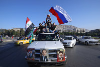Syrian government supporters wave Syrian, Iranian and Russian flags as they chant slogans against U.S. President Trump during demonstrations following a wave of U.S., British and French military strikes, in Damascus, Syria, on April 14, 2018. (AP Photo/Hassan Ammar)