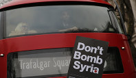 Protesters hold up a placard as bus passengers look on during a demonstration, Friday, April 13, 2018, in London, organized by the Stop the War Coalition against possible military intervention or bombing by western allies in Syria. (AP Photo/Alastair Grant)