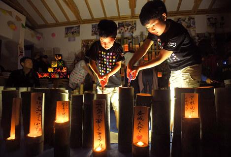 熊本地震2年を迎えて竹灯籠に火をともす子供たち=熊本県益城町の木山仮設団地で2018年4月14日午後7時2分、徳野仁子撮影