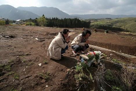 高台の住宅地跡で、熊本地震による土砂崩れで亡くなった人を悼み、献花して手をあわせる地元住民=熊本県南阿蘇村で2018年4月15日午後4時16分、和田大典撮影