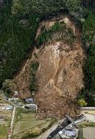 山が崩落し、民家が巻き込まれ、3世帯6人が安否不明となった現場=大分県中津市耶馬渓町で2018年4月11日、本社ヘリから