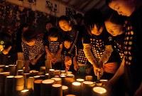熊本地震の発生から2年となり、追悼の思いをこめて竹灯籠に火をともす木山仮設団地の人たち=熊本県益城町で2018年4月14日、徳野仁子撮影