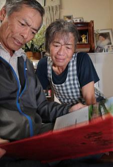 本震で亡くなった河添由実さんと親友の写真が載った卒業アルバムを見つめる(左から)父・敏明さんと母・登志子さん=熊本県益城町で2018年4月14日午後5時59分、和田大典撮影