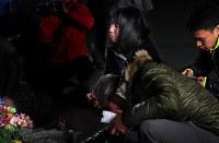 本震の発生時刻にあわせて大和晃さんの車が発見された現場近くを訪れた母・忍さん(奧)たち家族=熊本県南阿蘇村で2018年4月16日午前1時13分、和田大典撮影