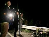 本震発生時刻の午前1時25分にあわせて大和晃さんの車が見つかった現場近くを訪れた(右から)父・卓也さん、母・忍さん、兄・翔吾さん。卓也さんは「2年たったが、この日のこの時間帯に来ると、(地震発生が)どうしてその時間帯なのか、どうしてあの子なのか、悔しいという気持ちはなかなか変わりにくい」と話した=熊本県南阿蘇村で2018年4月16日午前1時21分、和田大典撮影