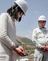 本震で亡くなった大和晃さんの車が見つかった現場近くを訪れ献花し、現場に一番近い所にあった石を持ち帰った母・忍さん(左)と父・卓也さん。忍さんは「今後、もっと近くに寄れたらそこの石と替えるつもり」と話した=熊本県南阿蘇村で2018年4月16日午後0時57分、和田大典撮影