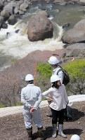 花束を手に、本震で亡くなった大和晃さんの車が見つかった現場近くを訪れた母・忍さん(右手前)たち家族=熊本県南阿蘇村で2018年4月16日午後0時44分、和田大典撮影