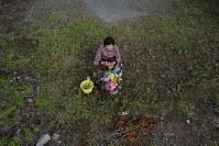 「京子ちゃん今年は来たけんね。長いこと来れんだったけん」本震で亡くなった島崎京子さん宅跡に花などを手向ける友人の永田成子さん(74)。昨年のこの日は病気で入院中で来ることができなかった。「3日前に京子さんが夢に出てきてにこにこ笑っていた。一緒に庭の花を手入れしていたのが懐かしいです」=熊本県益城町で2018年4月16日午後5時22分、和田大典撮影