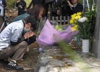 熊本地震の本震で九州電力黒川第1発電所の貯水槽が損壊して大量の水が流れ出た新所地区で、亡くなった2人を悼み花を合わせる地元の人たち=熊本県南阿蘇村で2018年4月16日午前10時10分、徳野仁子撮影