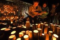 熊本地震から2年を迎え、本震の発生時刻に向けて竹灯籠に火を灯す木山仮設団地の人たち=熊本県益城町で2018年4月16日午前1時18分、徳野仁子撮影