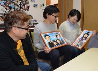 森琢磨さん(左)から贈られた花梨ちゃんの絵を見つめる宮崎貴士さん(中央)とさくらさん=熊本県合志市で2018年4月15日午前10時0分、山下俊輔撮影