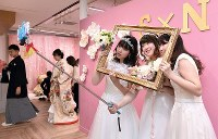 Women in wedding garb pose for a photo at