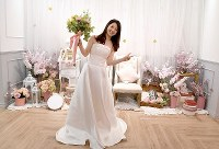 A woman in a wedding dress strikes a pose at