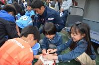 山越康平選手(奥中央)とともにブラジルに贈るボールを磨く子供たち=さいたま市大宮区のNACK5スタジアム大宮で2018年4月15日、錦織祐一撮影