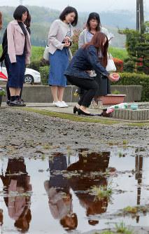 本震で脇志朋弥さんが亡くなったアパート跡を訪れ、脇さんが好きだったリンゴを供える大学の同級生たち