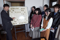 学生記者たちの前で将棋の駒を動かす棋士の杉本昌隆七段(左)=名古屋市北区で2018年3月16日、兵藤公治撮影