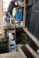 手作りの水車などで水力発電を成功させた熊田得男さん(右)ら=兵庫県豊岡市で、高田房二郎撮影