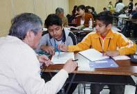 ネパールから来た中学生の兄弟に日本語を教えるチューター(左)=奈良市中部公民館で、新宮達撮影