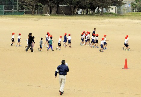 Students at Futenma No. 2 Elementary School in Ginowan, Okinawa Prefecture, take part in an evacuation drill in preparation for the approach of a U.S. military aircraft in this file photo taken on Jan. 18, 2018. (Mainichi)