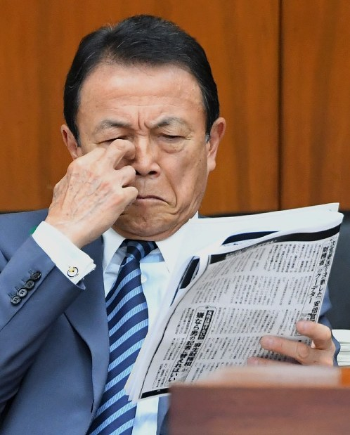 Finance Minister Taro Aso holds copies of a weekly magazine article reporting sexual harassment allegations against Finance Vice Minister Junichi Fukuda, at the Diet building on April 18, 2018. (Mainichi)