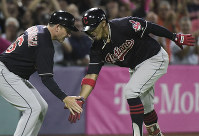 Cleveland Indians' infielder Francisco Lindor, right, celebrates his home run against the Minnesota Twins during the fifth inning of game one of a two-game MLB Series at Hiram Bithorn Stadium in San Juan, Puerto Rico, on April 17, 2018. (AP Photo/Carlos Giusti)