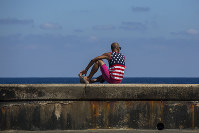 A man wearing a shirt with the stars and stripes sits on the Malecon in Havana, Cuba, on April 18, 2018. (AP Photo/Desmond Boylan)