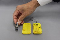 An exploded battery and a personal alarm buzzer are seen in Tokyo's Minato Ward on April 19, 2018. (Mainichi)