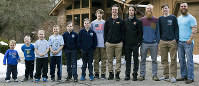 In this Feb. 16, 2018 photo, from left to right, brothers Francisco, 2, Tucker, 4, Luke, 6, Charlie, 8, Gabe, 11, Wesley, 9, Calvin, 13, Drew, 20, Tommy, 16, Zach, 22, Vinny, 15, and Ty Schwandt, 25, pose for a portrait at the Schwandt household in Grand Rapids, Mich. The only brother not pictured is Brandon, 18. (Casey Sykes /The Grand Rapids Press via AP)