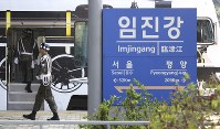 A South Korean army solider passes by a signboard showing the distance to North Korea's capital Pyongyang and to South Korea's capital Seoul from Imjingang Station in Paju, South Korea, near the border with North Korea, on April 20, 2018. (AP Photo/Ahn Young-joon)