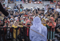 People use their cell phones to take pictures as a Shariah law official whips a woman who is convicted of prostitution during a public caning outside a mosque in Banda Aceh, Indonesia, on April 20, 2018. (AP Photo/Heri Juanda)
