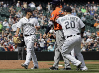 Seattle Mariners first baseman Daniel Vogelbach (20) tags out Houston Astros' Evan Gattis, second from right, for the third out of a triple play as Mariners' starting pitcher Marco Gonzales, left, looks on during the fourth inning of a baseball game, on April 19, 2018, in Seattle. (AP Photo/Ted S. Warren)