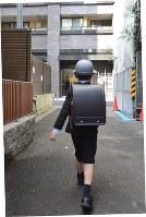 スーツを着て、新しいランドセルを背負い入学式に向かう男児=東京都内で