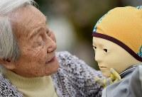 「テレノイド」に語りかける内田文子さん=兵庫県尼崎市で2018年4月5日、久保玲撮影