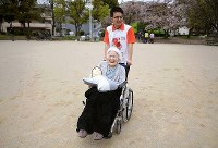 「テレノイド」を持ち、公園内を散歩する三木スエノさん=兵庫県尼崎市で2018年4月5日、久保玲撮影