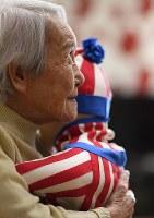 「抱きしめて」とお願いされ、「テレノイド」をそっと抱きしめる内田文子さん=兵庫県尼崎市で2018年4月5日、久保玲撮影