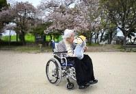 膝に乗せた「テレノイド」に語りかける内田文子さん=兵庫県尼崎市で2018年4月5日、久保玲撮影