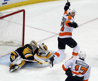 Philadelphia Flyers' Scott Laughton (21) begins to celebrate after a shot by Sean Couturier got past Pittsburgh Penguins goaltender Matt Murray (30) during the third period in Game 5 of an NHL first-round hockey playoff series in Pittsburgh, on April 20, 2018. (AP Photo/Gene J. Puskar)