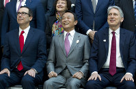 Foreground from left, U.S. Treasury Secretary Steve Mnuchin, Japan's Finance Minister Taro Aso and U.K. Chancellor of the Exchequer Philip Hammond sit with others for the group photo of International Monetary Fund governors at the World Bank/IMF Spring Meetings in Washington, on Saturday, April 21, 2018. (AP Photo/Jose Luis Magana)