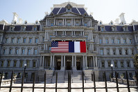 The U.S. and French flags are displayed on the Eisenhower Executive Office Building, Friday, April 20, 2018, in Washington. President Donald Trump plans to celebrate nearly 250 years of U.S.-French relations by hosting President Emmanuel Macron at a glitzy White House state dinner on Tuesday. It's the first state visit and the first big soiree of the Trump era in Washington. (AP Photo/Alex Brandon)