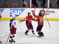 Washington Capitals center Nicklas Backstrom (19), of Sweden, celebrates his winning goal with T.J. Oshie (77) in overtime of Game 5 of an NHL first-round hockey playoff series as Columbus Blue Jackets center Pierre-Luc Dubois (18) skates by, Saturday, April 21, 2018, in Washington. (AP Photo/Nick Wass)