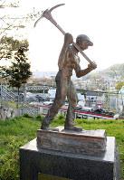 家並みや山を望む草地にひっそりとある「神戸電鉄敷設工事朝鮮人労働者の像」。斜面下を数分おきに電車が通る=神戸市兵庫区で、木田智佳子撮影