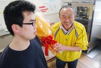 39年の教員生活を終えた増住恵さん(右)に、楠高校の卒業生から感謝の気持ちを込めて花束が贈られた=神戸市兵庫区で、桜井由紀治撮影