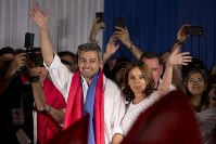 Paraguay's President Elect Mario Abdo Benitez, left, of the Colorado Party, and his wife Silvana Lopez Moreira wave at supporters during celebrations at the party headquarters' in Asuncion, Paraguay, on April 22, 2018. (AP Photo/Jorge Saenz)