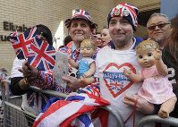 Royal fans John Loughrey, right, and Terry Hutt pose for a photo opposite the Lindo wing at St Mary's Hospital in London London, Monday, April 23. (AP Photo/Kirsty Wigglesworth)
