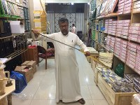 A shop owner holds up a blunt sword that Saudi men wear with formal attire at a shop where the item is sold in Riyadh, Saudi Arabia, on April 18, 2018. Each sword costs 150 Saudi riyals (about 4,500 yen), but the more expensive ones are said to go for as much as 10,000 riyals, or 300,000 yen. (Mainichi)