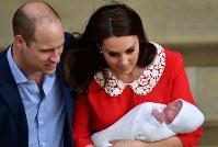 出産した第3子の王子を抱っこし退院する英王室のキャサリン妃(右)とウィリアム王子=ロンドンで2018年4月23日、ロイター