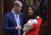 出産した第3子の王子を抱っこして写真撮影に応じる英王室のキャサリン妃(右)とウィリアム王子=ロンドンで2018年4月23日、AP
